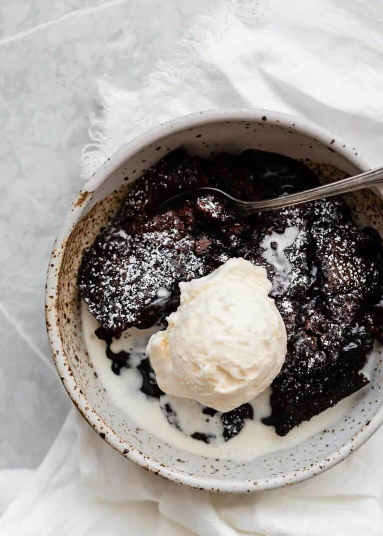 Dark Chocolate Molten Lava Cobbler Cake with Toffee Bits in a bowl with a scoop of vanilla bean ice cream