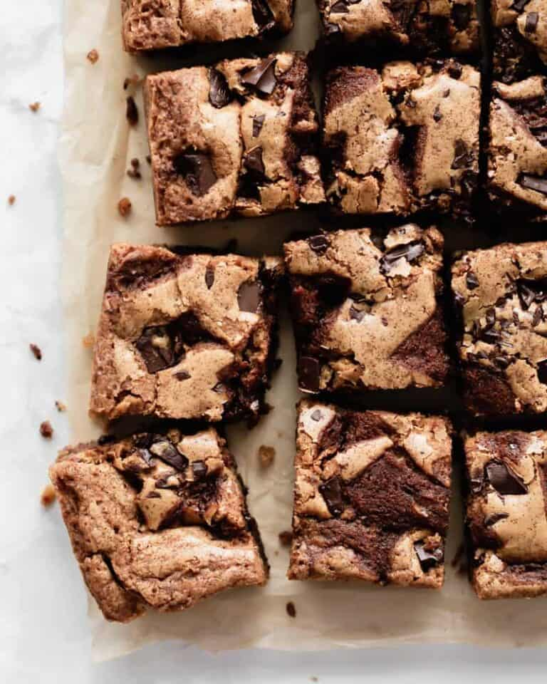 Brown butter chocolate chunk butterscotch blondies cut into squares on parchment paper