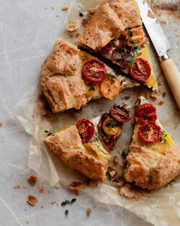 Slices of heirloom tomato galette with ricotta and pistachio pesto
