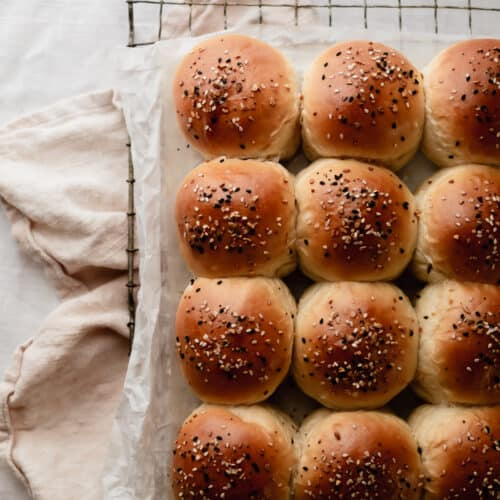 One dozen milk bread dinner rolls topped with everything but the bagel seasoning sitting on a cooling rack
