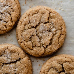 Four baked peanut butter cookies sitting on top of parchment paper