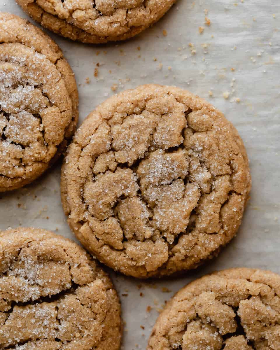 Five freshly baked peanut butter cookies on top of parchment paper