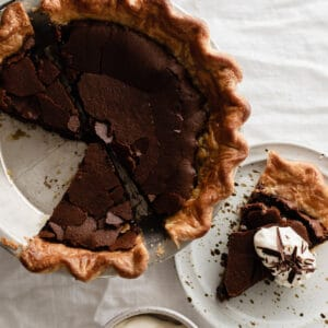 chocolate chess pie with a slice taken out of it sitting on top of a white tablecloth