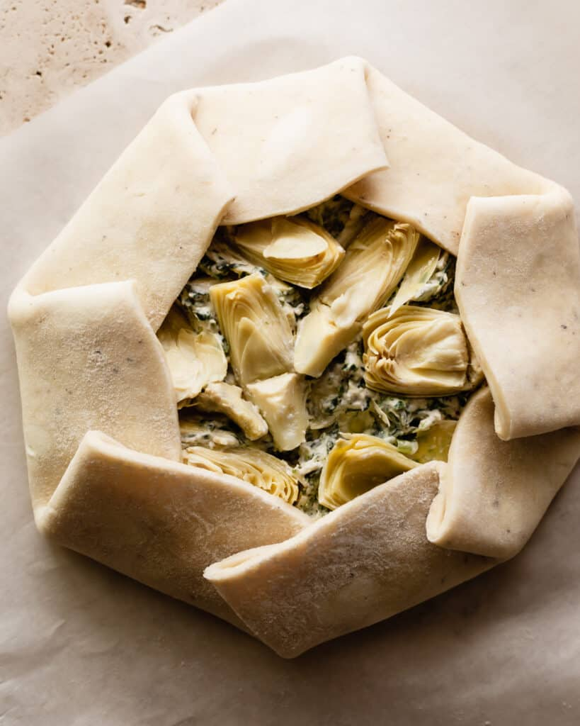 Overhead shot of a galette crust filled with spinach and artichoke dip with the crust overlapping and folded over
