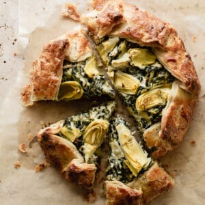 Overhead shot of a savory spinach and artichoke galette sitting on parchment paper